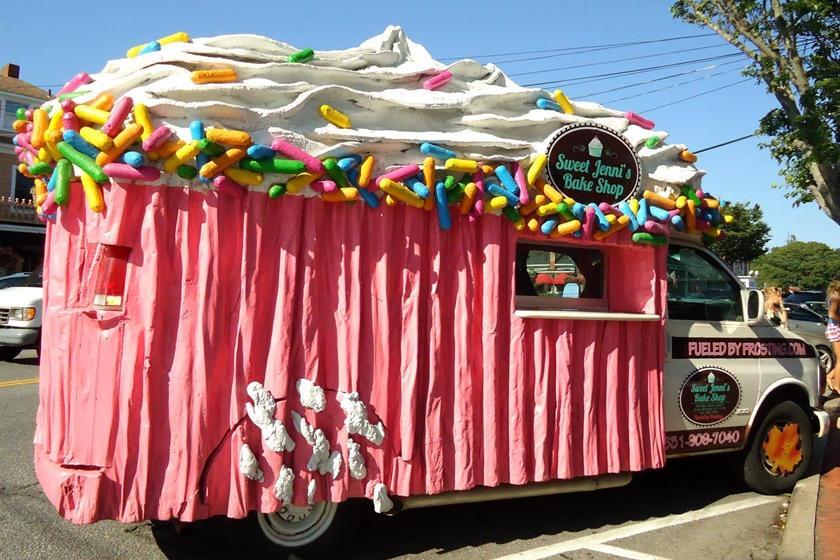 """Một người đàn ông tên Jenni's đã không mất nhiều thời gian và công sức để trang trí cho """"cửa hàng""""di động của mình. Chỉ cần phủ một lớp vải với hình thù của một chiếc bánh cupcakes (kem bơm và sữa tươi) và trang trí lại phần đầu của chiếc xe thì người đàn ông trên có thể mang """"cửa hàng của mình đi khắp mọi nơi trên đường phố New York (Hoa Kỳ). Ảnh: Carbuzz"""