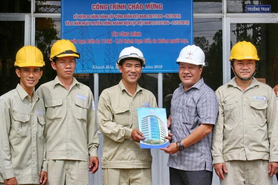 Ông Nguyễn Mạnh Thông chủ tịch Công đoàn công ty Điện lực Khánh Hòa và CBCN trạm biến áp 110KV-E30 găn biển công trình chào mừng 90 năm thành lập Công đoàn Việt Nam. Ảnh: P.L