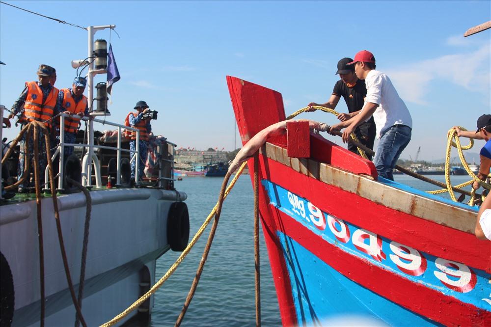 Cán bộ, chiến sĩ tàu CSB 4032 hỗ trợ ngư dân thả dây để cập cầu cảng. Ảnh: N.CƯỜNG