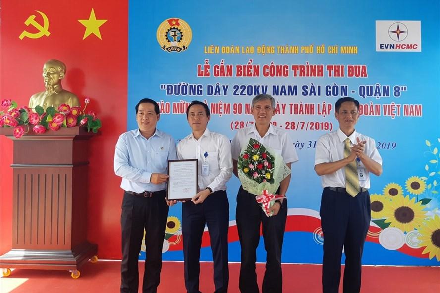 Ông Kiều Ngọc Vũ (bìa trái), Phó Chủ tịch LĐLĐ TPHCM và ông Bành Đức Hoài (bìa phải), Phó Tổng giám đốc EVNHCMC, trao quyết định công nhận công trình thi đua cấp LĐLĐ TPHCM cho đại diện đơn vị thuộc EVNHCMC. Ảnh Nam Dương.