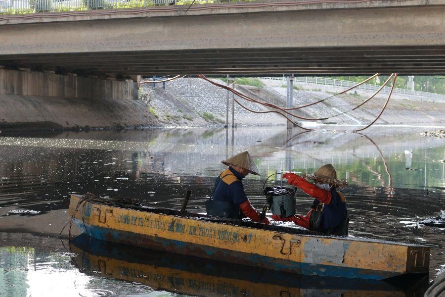 Những người đàn ông trong đoàn sẽ tiến hành múc bùn và rác thải ở dưới lòng sông đổ vào thuyền. Sau đó, từng xô bùn sẽ được chuyền tay qua những nữ công nhân để đưa lên bờ mang đi nơi khác xử lý.