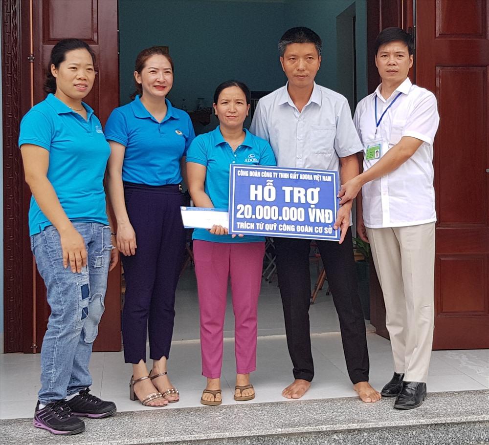Đại diện CĐ Công ty TNHH giầy ADORA Việt Nam troa tiền hỗ trợ cho gia đình chị Phạm Thị Lan. Ảnh: NT