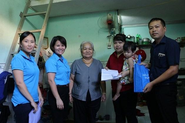Bà Nguyễn Hoàng Bảo Trân (thứ 2, bên trái sang) trao tiền hỗ trợ cho gia đình chị Nguyễn Thị Kiều.
