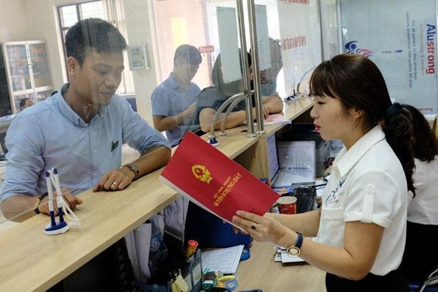 Hướng dẫn cho người dân làm thủ tục hành chính tại Bộ phận một cửa UBND huyện Sóc Sơn. Ảnh: Kinh tế đô thị
