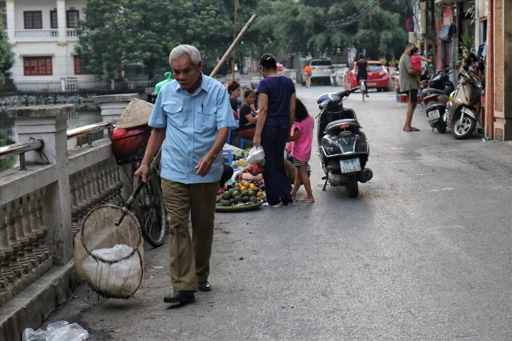 Sau khi chợ tan, ông Luyện lại thu gom rác rồi chuyển vào thùng.