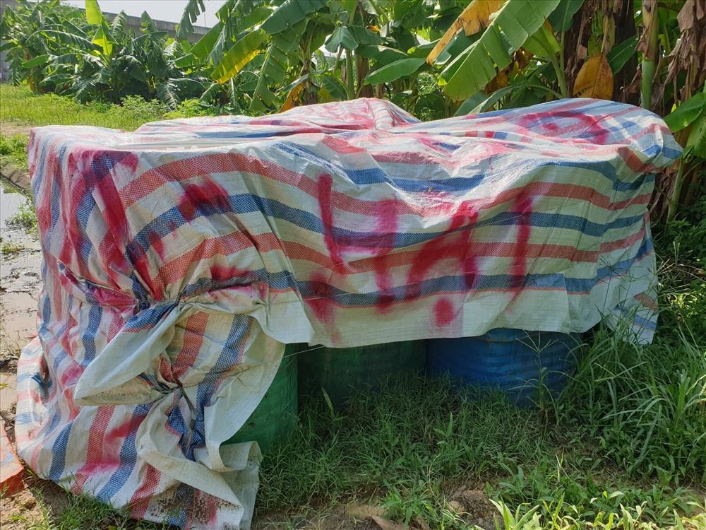 Các thùng phuy chứa rác thải nguy hại được quây kín bạt tại km19 Đại lộ Thăng Long. Ảnh: Phạm Đông