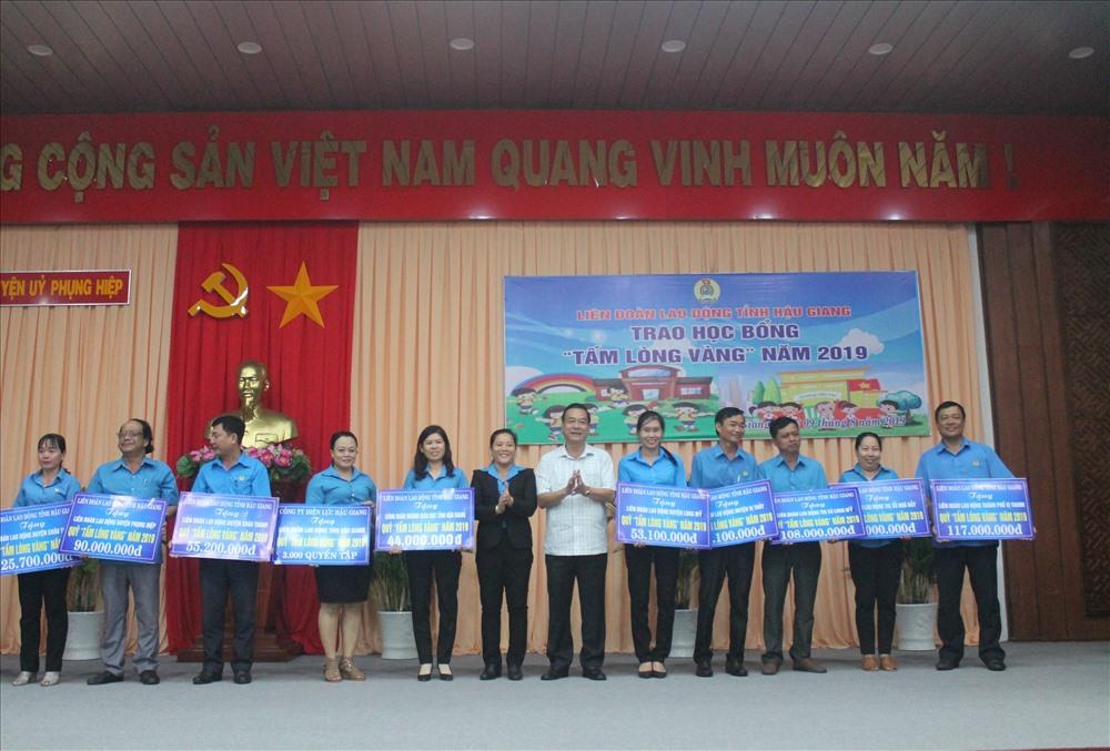 Ông Huỳnh Thanh Tạo và Bà Lê Thị Thanh Lam - trao bảng tượng trưng Quỹ tấm lòng vàng cho các LĐLĐ cấp huyện và tương đương. Ảnh: Thành Nhân