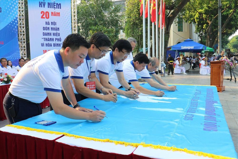 Các đại biểu, khách mời và bạn bè quốc tế thực hiện nghi thức ký cờ hoà bình
