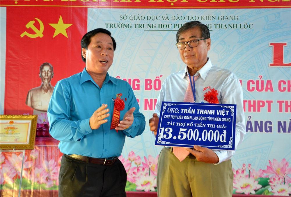 Ông Trần Thanh Việt (trái) trao bảng tượng trưng 1.500 quyển tập cho Trường THPT Thạnh Lộc. Ảnh: Lục Tùng