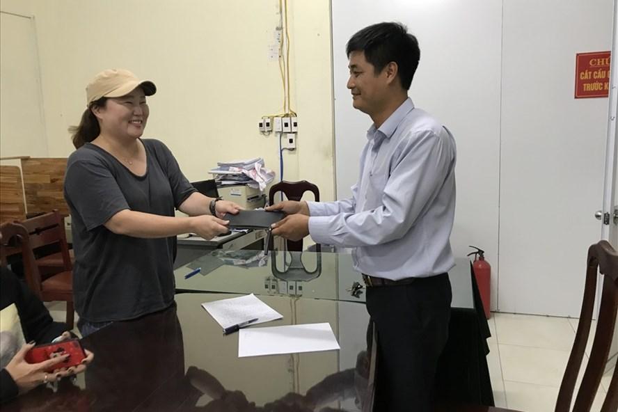 Đại diện hãng taxi Hàng Không trao trả tài sản lại cho du khách Hàn Quốc bỏ quên trên xe. ảnh: V.X
