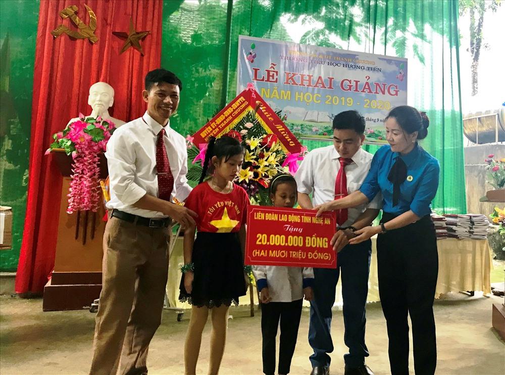 Phó Chủ tịch LĐLĐ tỉnh Nghệ An Nguyễn Thị Thu Nhi (bìa phải) tặng quà cho học sinh huyện Thanh Chương.