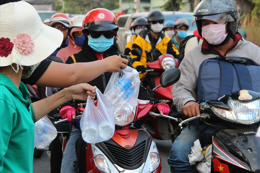 Một gia đình ở huyện Củ Chi mang nước suốt ra phát tặng người dân về quê. Ảnh: Đình Trọng