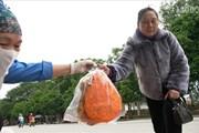 Người dân mua bánh đa gấc mong may mắn ngày đầu năm mới