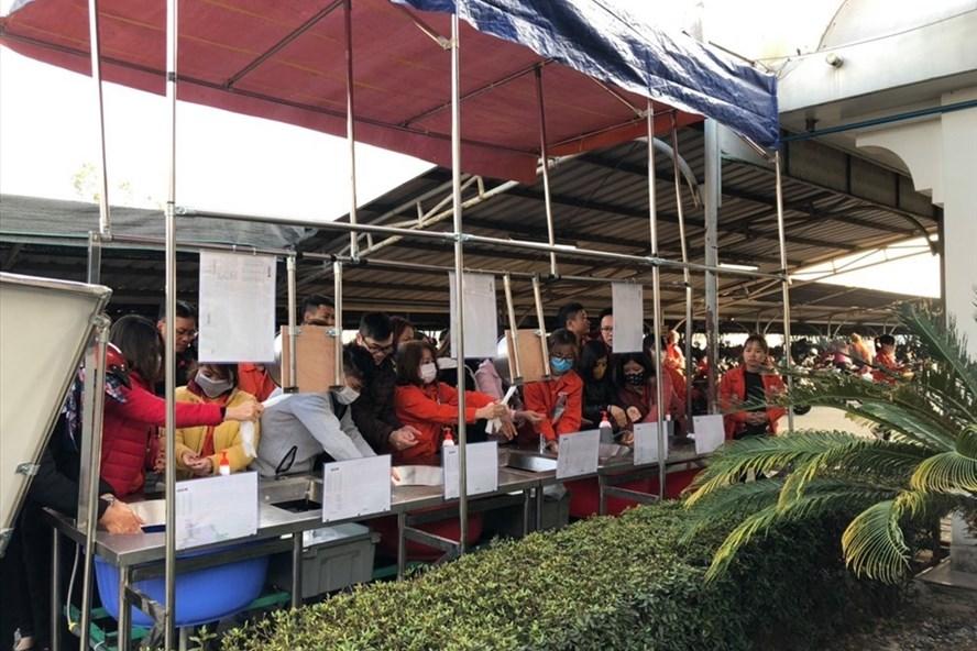Hàng nghìn công nhân xếp hàng rửa tay, đeo khẩu trang trước khi vào xưởng. Ảnh CTV