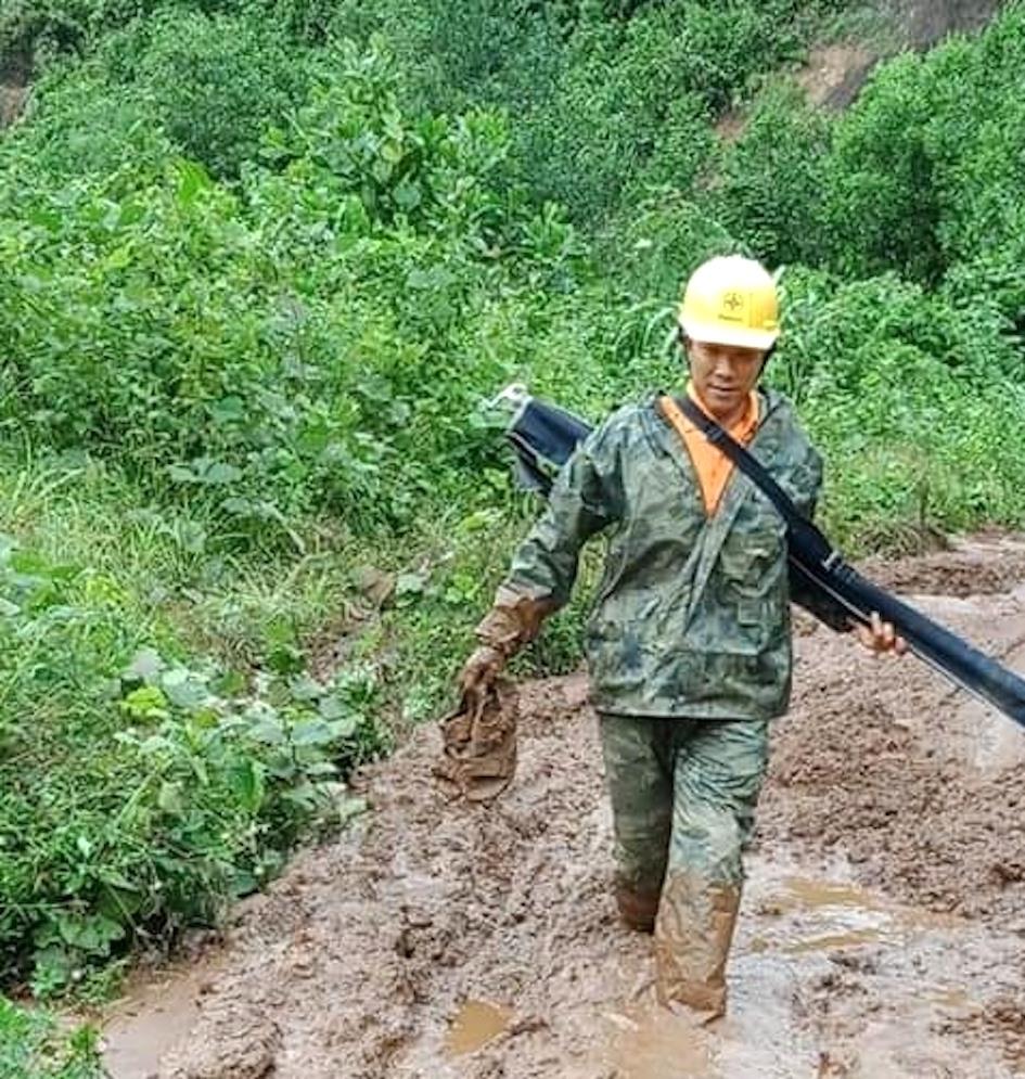 Người lao động Công ty điện lực Quảng Nam băng rừng, lội bùn đi khắc phục sự cố. Ảnh: PCQN