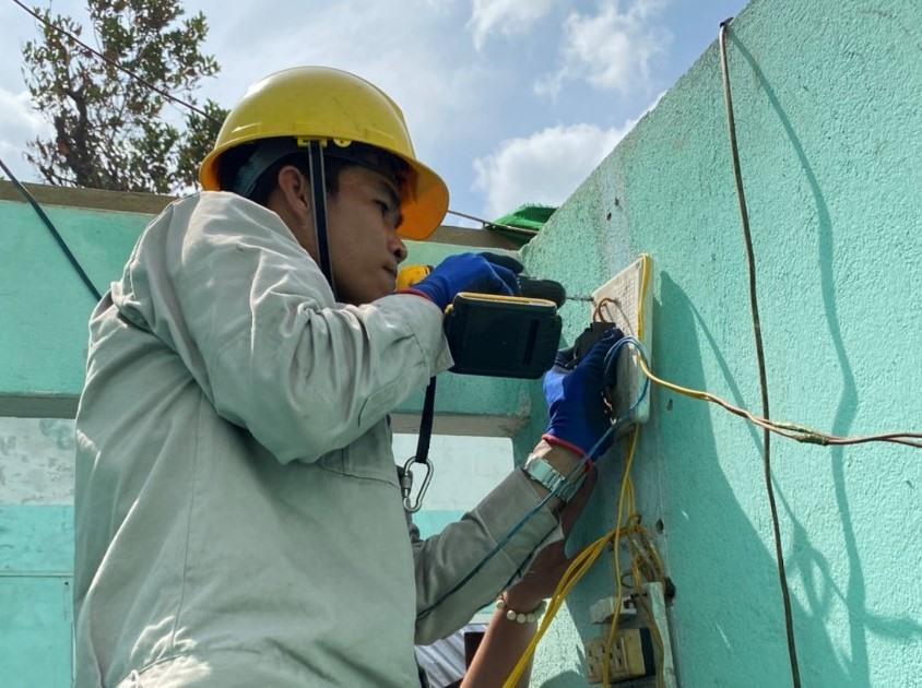Người lao động của EVNHCMC giúp người dân miền Trung bị lũ lụt sửa chữa lại hệ thống điện gia đình. Ảnh Đức Long