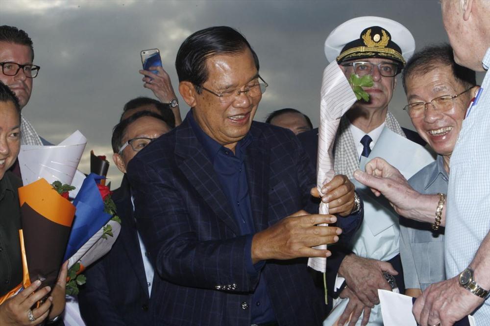 Thủ tướng Campuchia  Hun Sen tặng hoa cho một hành khách xuống tàu MS Westerdam. Hôm 13.2, Thủ tướng Hun Sen đã đồng ý cho tàu MS Westerdam cập cảng Sihanoukville sau khi Thái Lan, Nhật Bản, Đài Loan (Trung Quốc), Philippines và đảo Guam Mỹ) từ chối tiếp nhận. Ảnh: ABP.