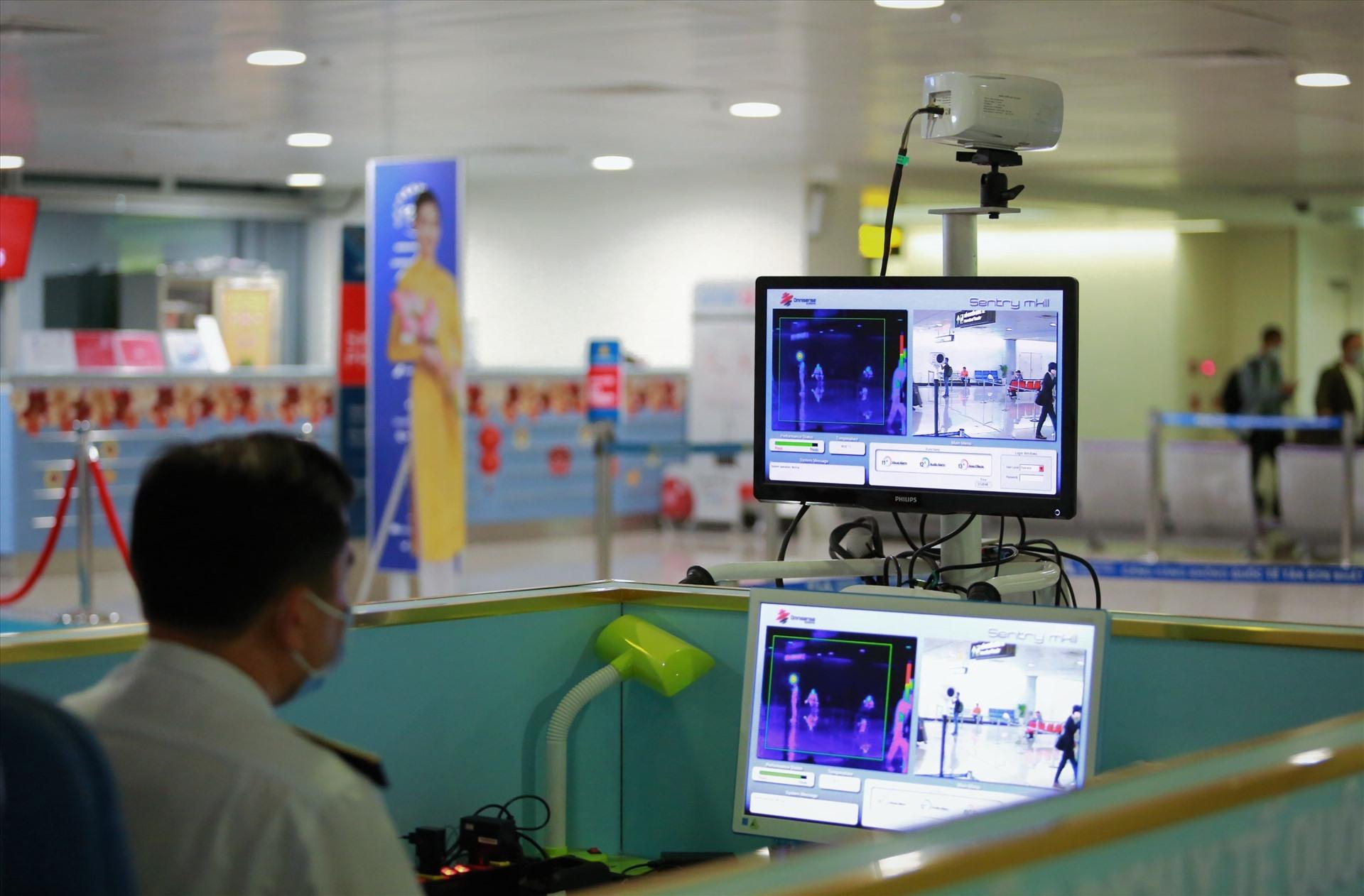 Cán bộ kiểm dịch túc trực tại máy đo thân nhiệt ở sân bay Tân Sơn Nhất.  Ảnh: Tú Chân