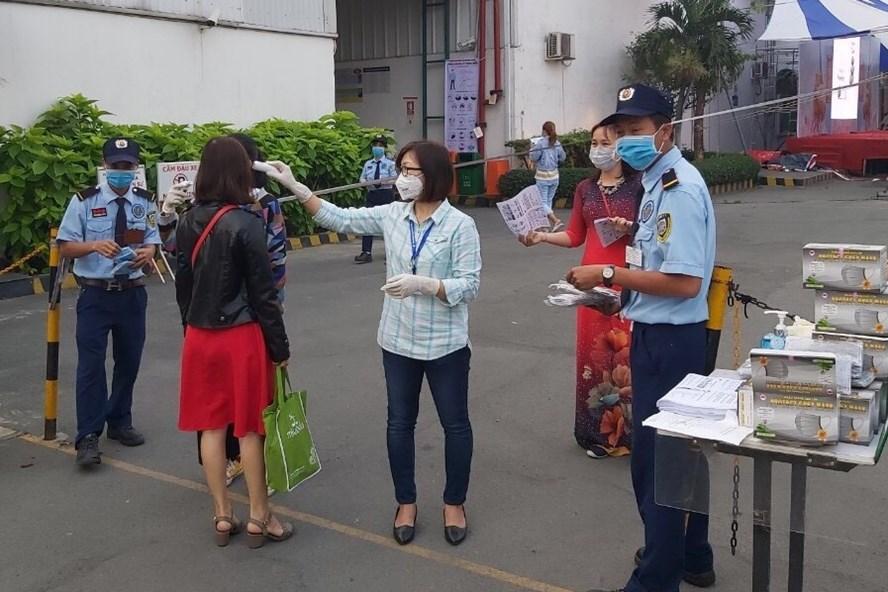 Công ty TNHH may mặc Bowker Việt Nam đo thân nhiệt phát khẩu trang cho công nhân từ cổng vào.