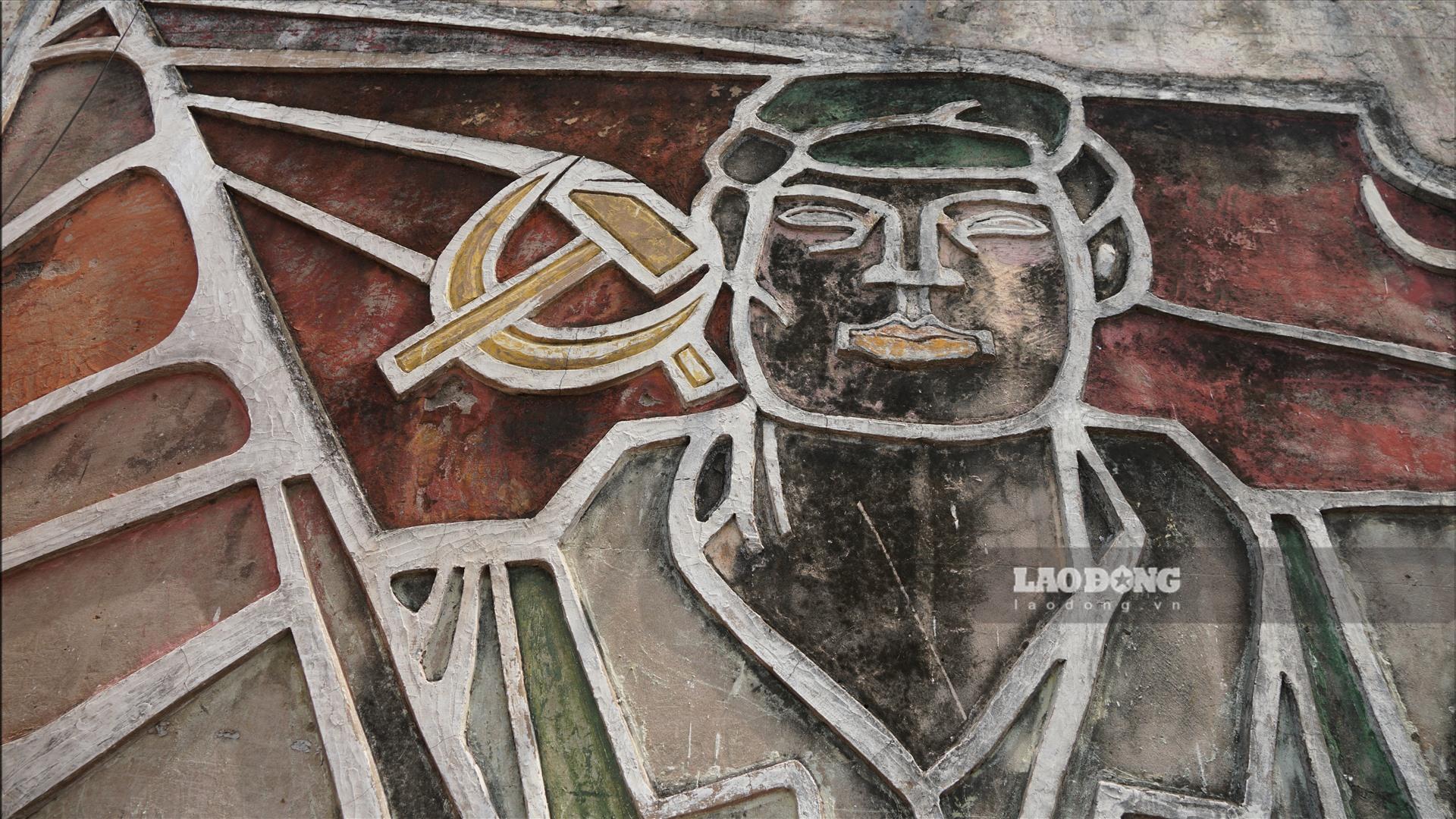 Bức phù điêu quý này là tác phẩm của hoạ sĩ tranh cổ động Trường Sinh, được thực hiện vào những năm 80 của thế kỉ trước. Tác phẩm nguyên bản gồm hai mặt khác nhau, một mặt được thực hiện bằng kĩ thuật ghép gốm, một mặt là bức phù điêu về sự đoàn kết Công - Nông - Trí.