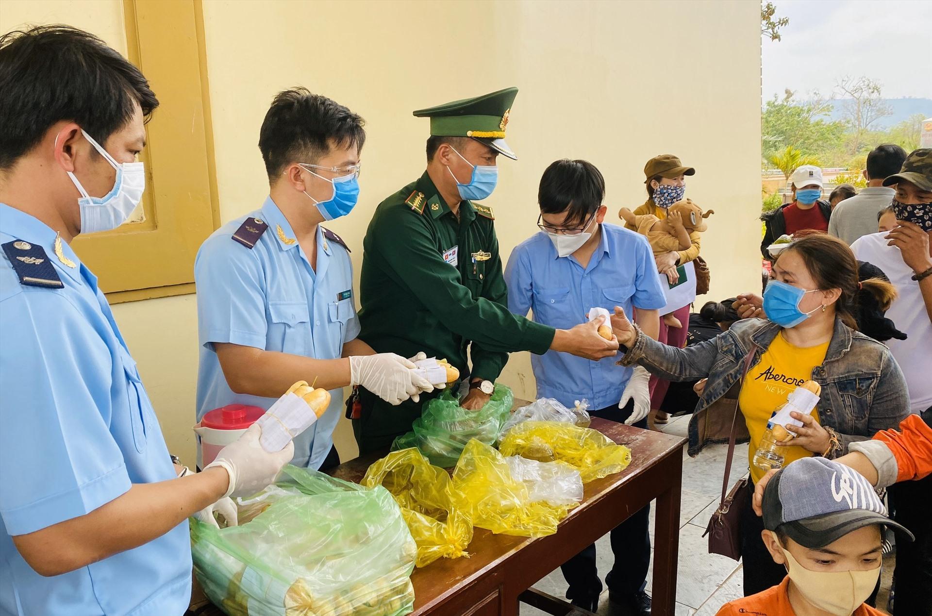 Đến giờ ăn, các lực lượng tại cửa khẩu sẽ phát thức ăn, nước uống cho từng người đang đợi làm thủ tục về khu cách ly tập trung.