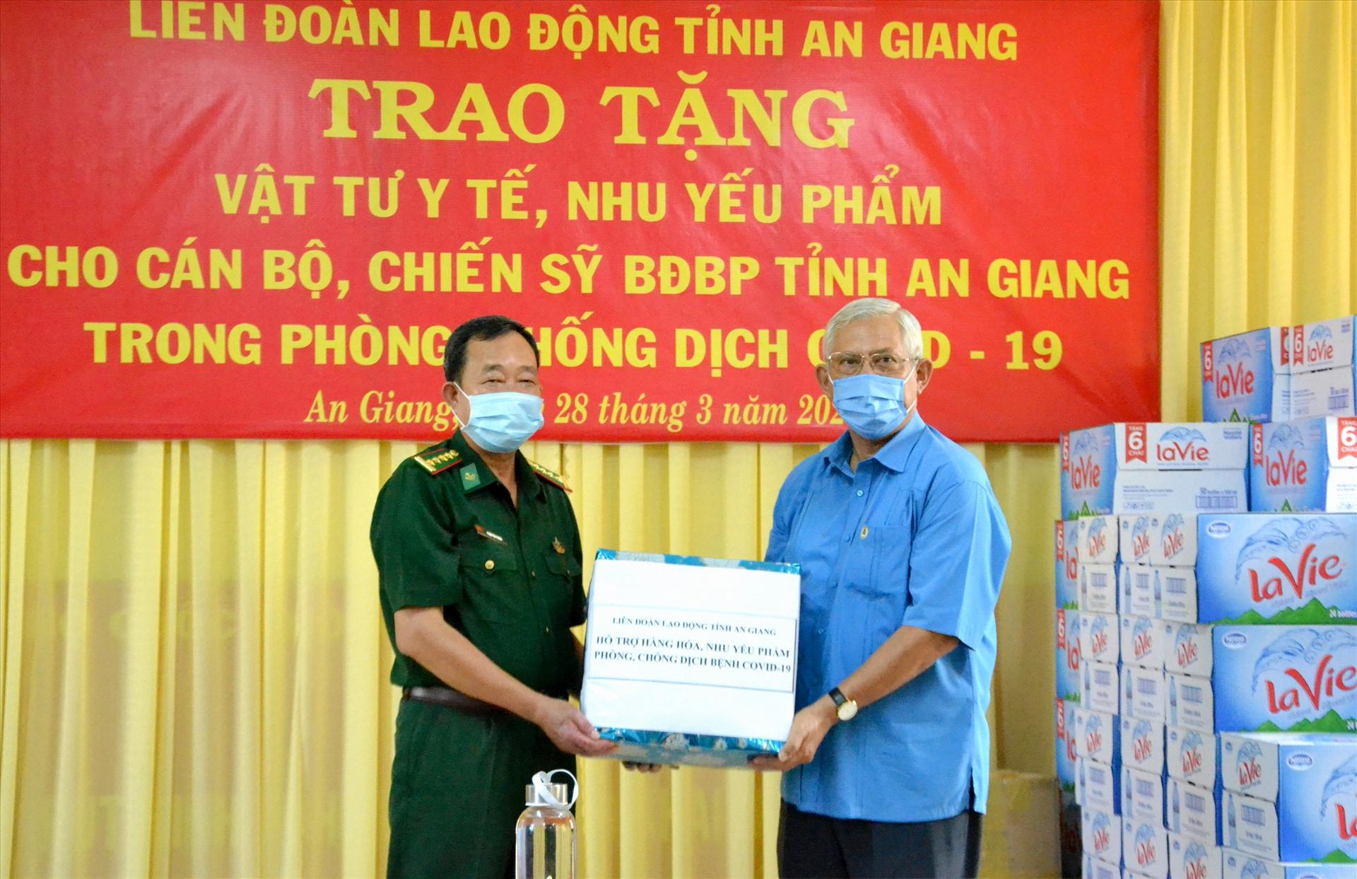 Chủ tịch LĐLĐ An Giang Nguyễn Thiện Phú trao hỗ trợ Bộ đội Biên phòng An Giang 150 chai nước sát khuẩn, 75 thùng mì ăn liền, 200 thùng nước tinh khiết, hộp cà phê. Ảnh: Lục Tùng