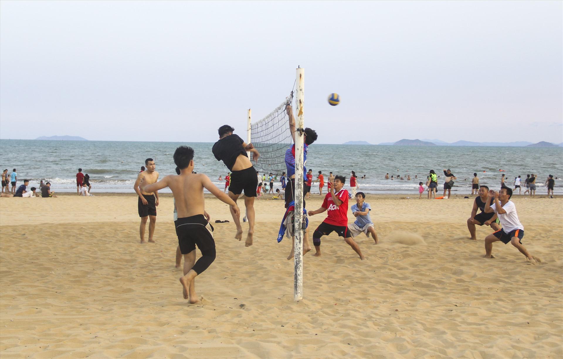 Bãi biển đông đúc người dân tụ tập thành từng nhóm: nhóm thì chơi đùa, nhóm tắm biển, nhóm đánh bóng chuyền....