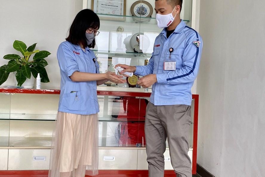 Công nhân viên Công ty Yamaha Motor Việt Nam thực hiện đeo khẩu trang, xịt nước diệt khuẩn trước khi vào làm việc. Ảnh: H.A