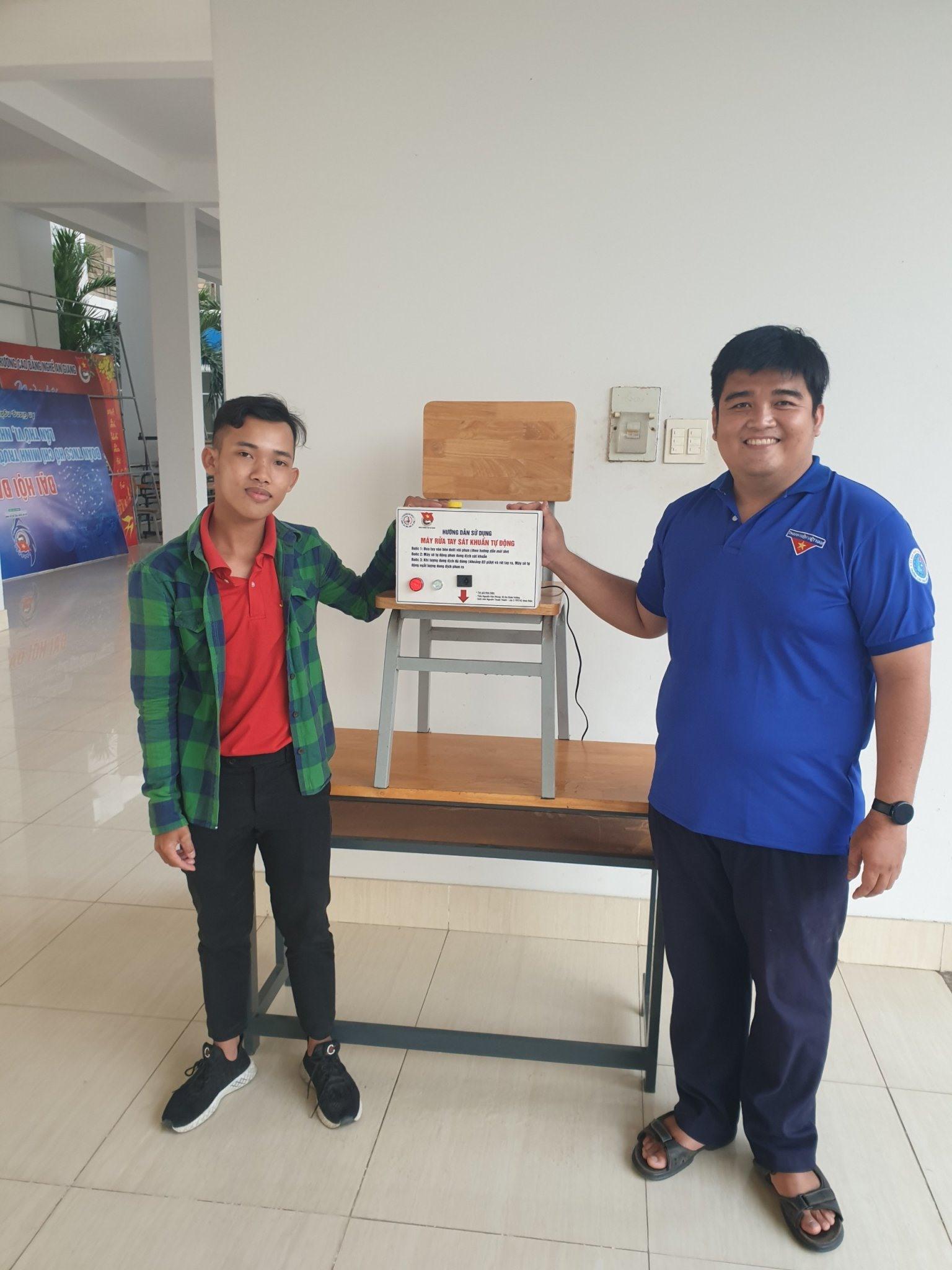 Nguyễn Thanh Phong (phải) bên sản phẩm máy rửa tay sát khuẩn tự động của mình. Ảnh: Cẩm Tú
