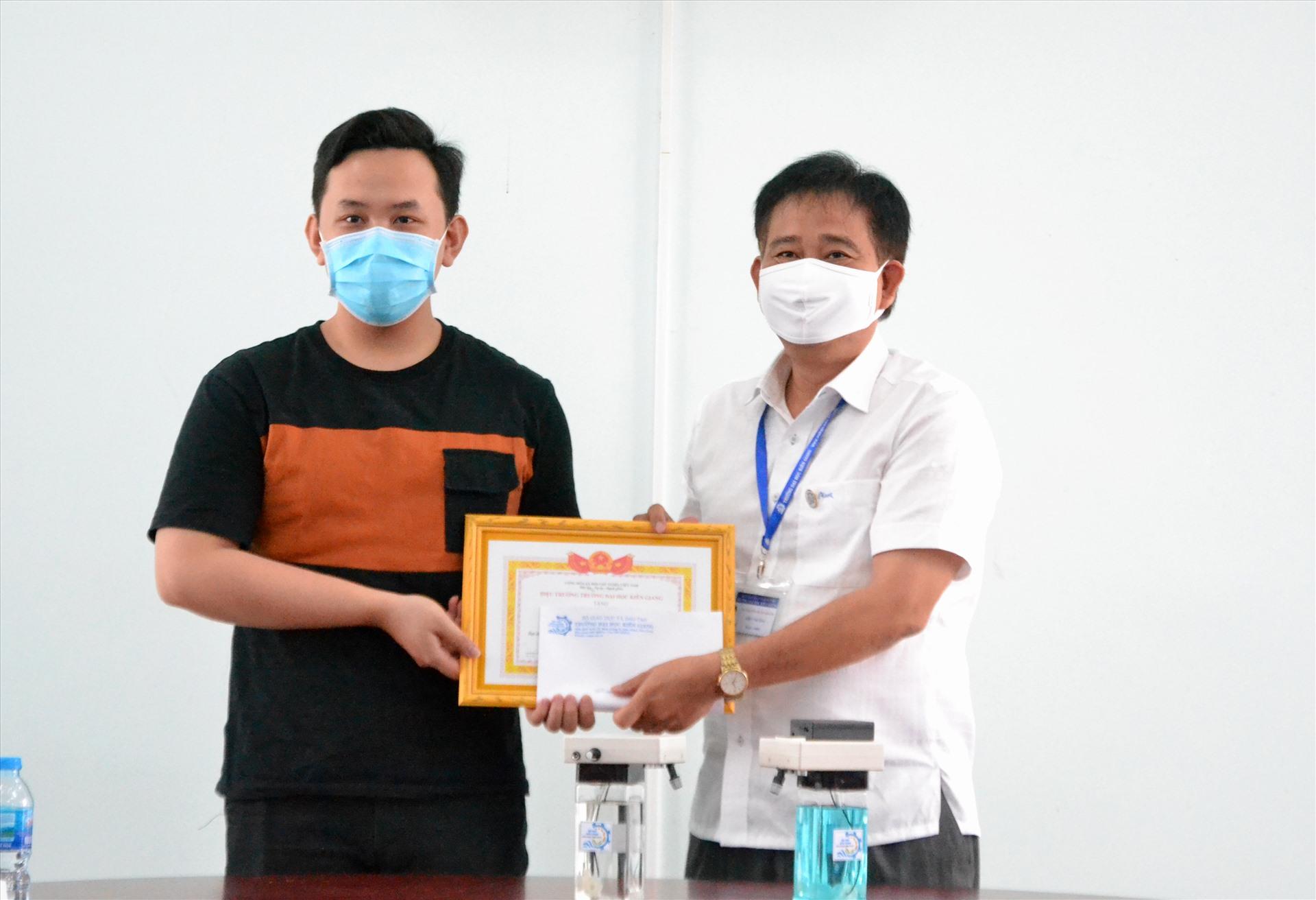 Tiến sĩ Nguyễn Tuấn Khanh (phải) khen thưởng đột xuất sinh viên Thái Minh Tín. Ảnh: LT