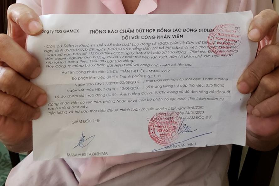 Bà Trần Thị Hiệp, 50 tuổi, công nhân Công ty TNHH Tomiya Summit Garment Export với mảnh giấy thông báo chấm dứt hợp đồng lao động trên tay. Ảnh: Hà Anh Chiến