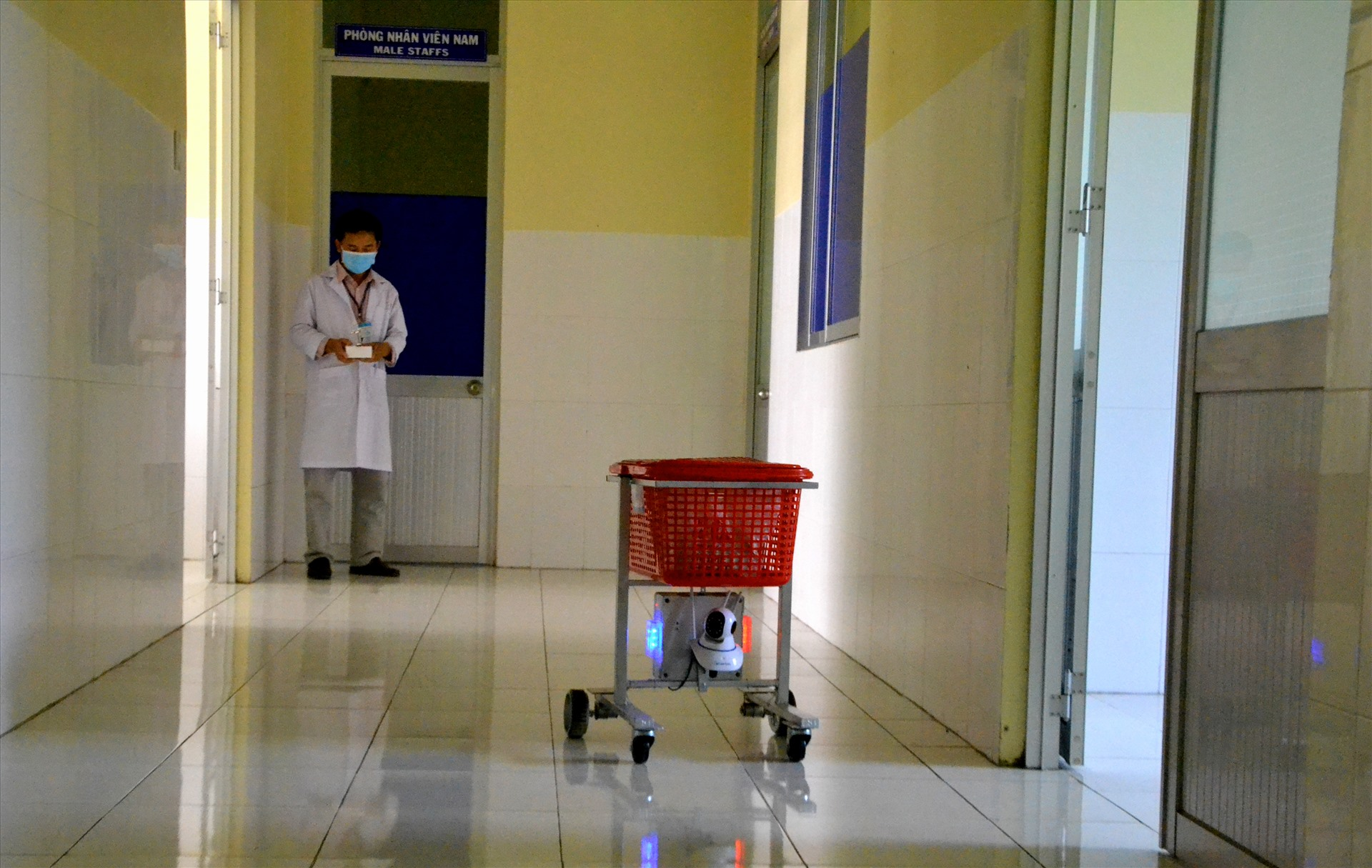 Thông qua điều khiển từ xa, điều hành robot mang vật dụng đến tận cửa phòng bệnh nhân. Ảnh: LT