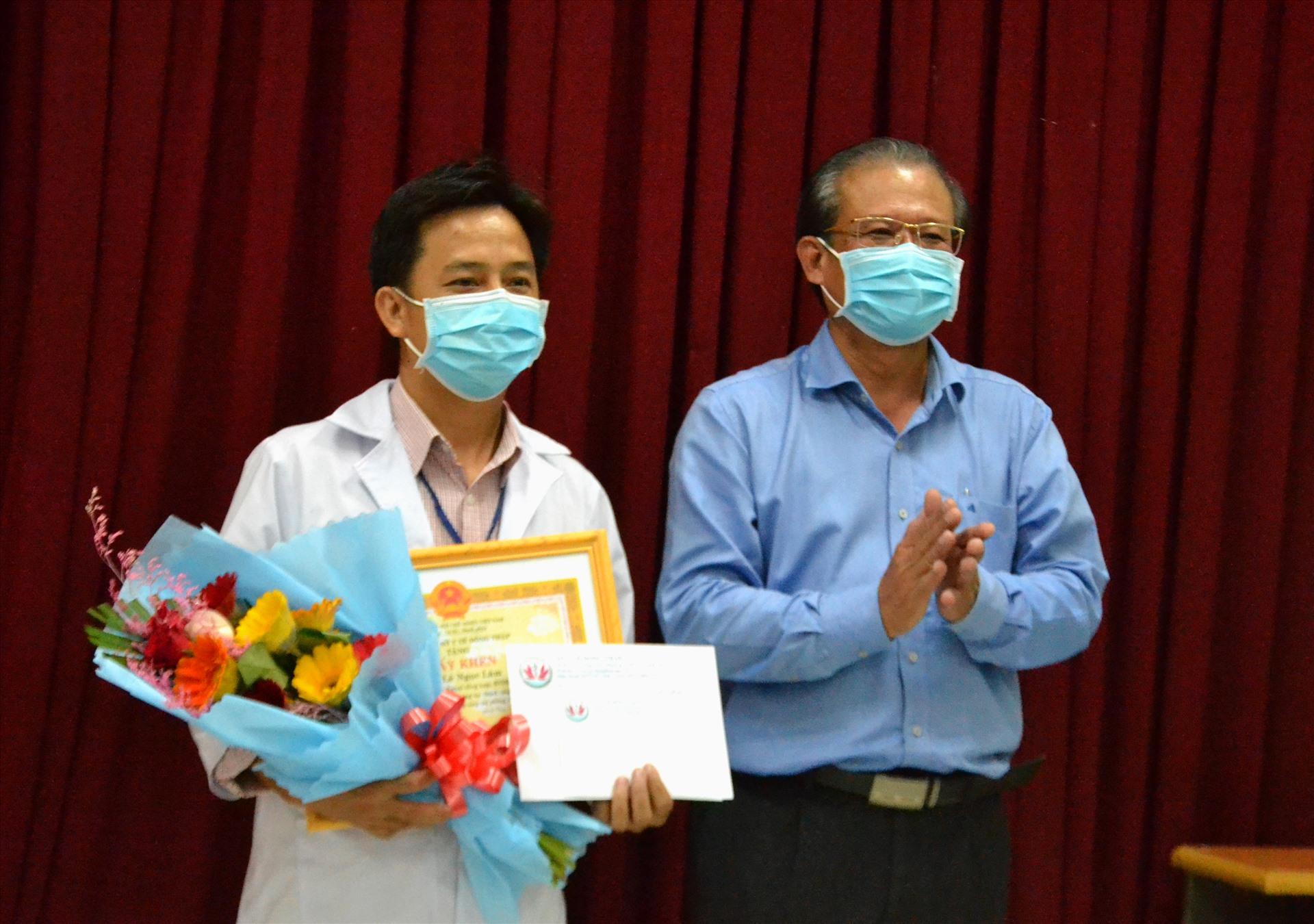 Bác sĩ Nguyễn Lâm Thái Thuận trao khen thưởng cho bác sĩ Lê Ngọc Lâm. Ảnh: LT