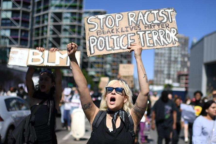 Người biểu tình mang theo những tấm khẩu hiệu phản đối phân biệt sắc tộc trong khi diễu hành bên ngoài Đại sứ quán Mỹ ở London hôm 31.5. Ảnh: AFP.