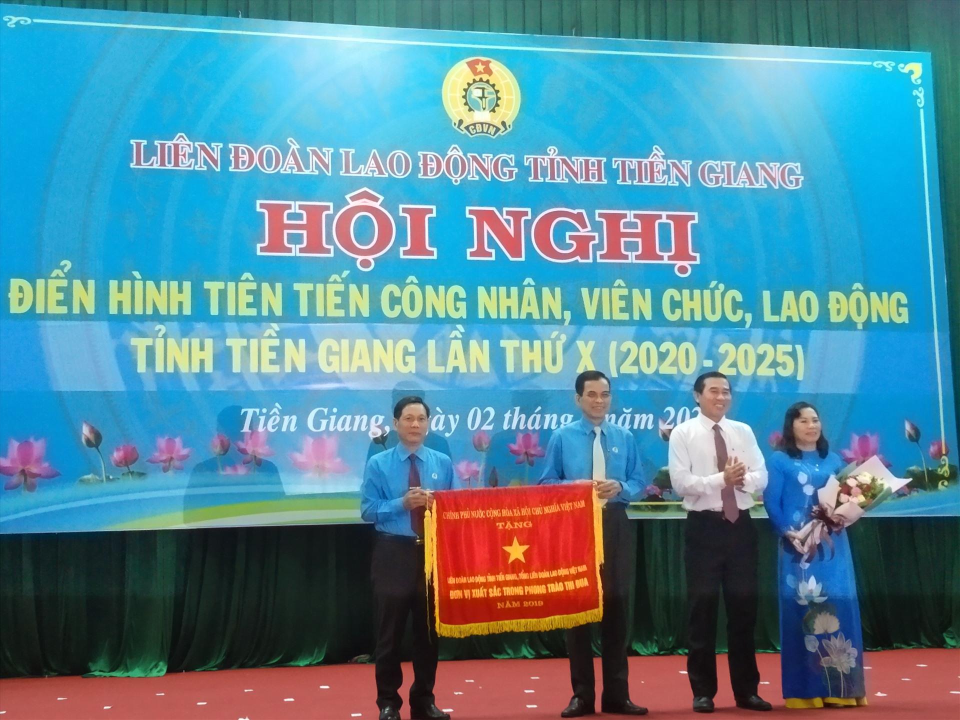 Chủ tịch UBND tỉnh Tiền Giang trao Cờ thi đua xuất sắc của Chính phủ cho LĐLĐ tỉnh Tiền Giang. Ảnh: K.Q