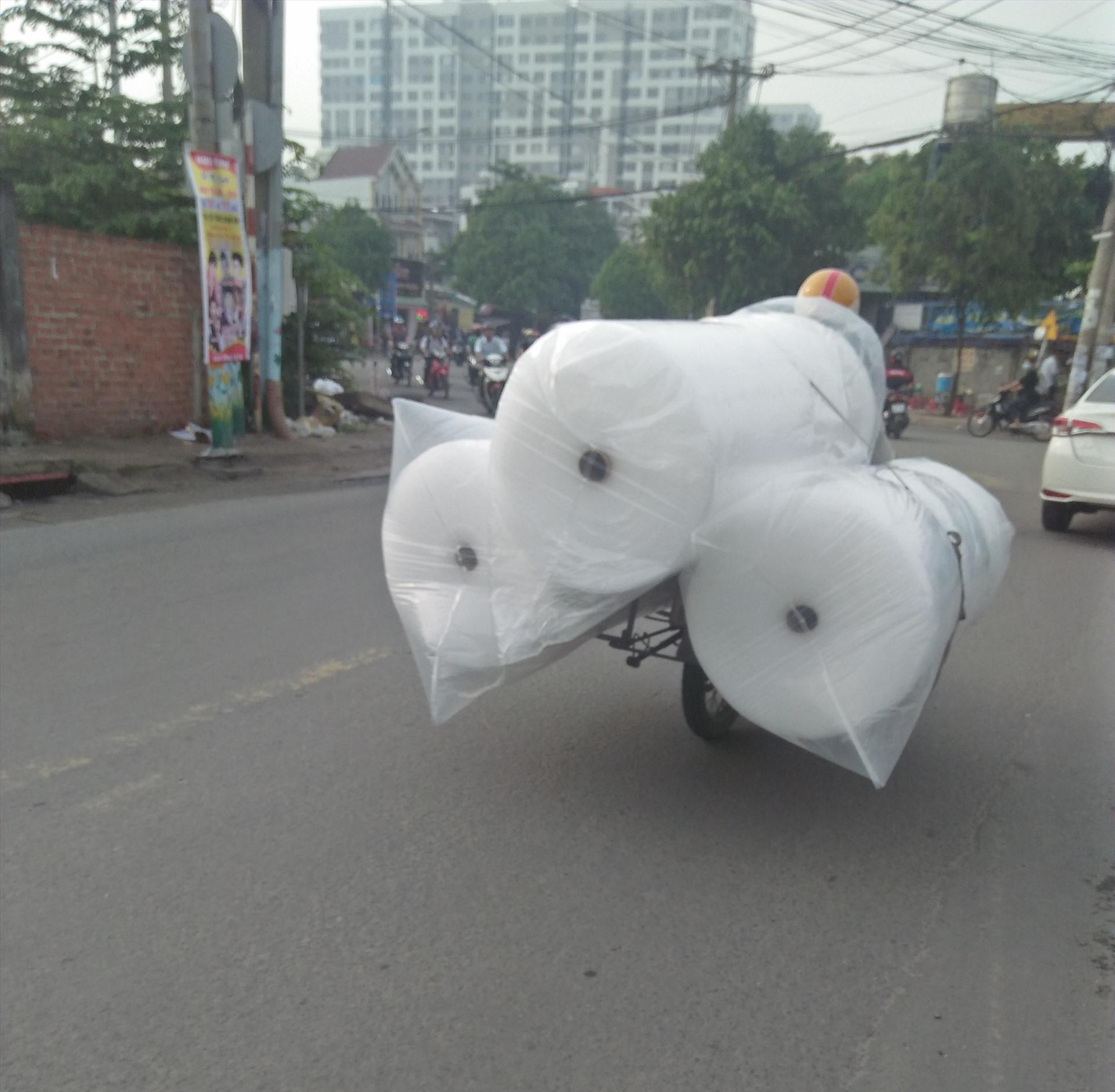 Người đi xe máy chở 3 cuộn hàng cồng kềnh chạy như xiếc trên đường Đào Trinh Nhất, Thủ Đức, TPHCM ( ảnh chụp sáng 30.6). Ảnh: Minh Khang