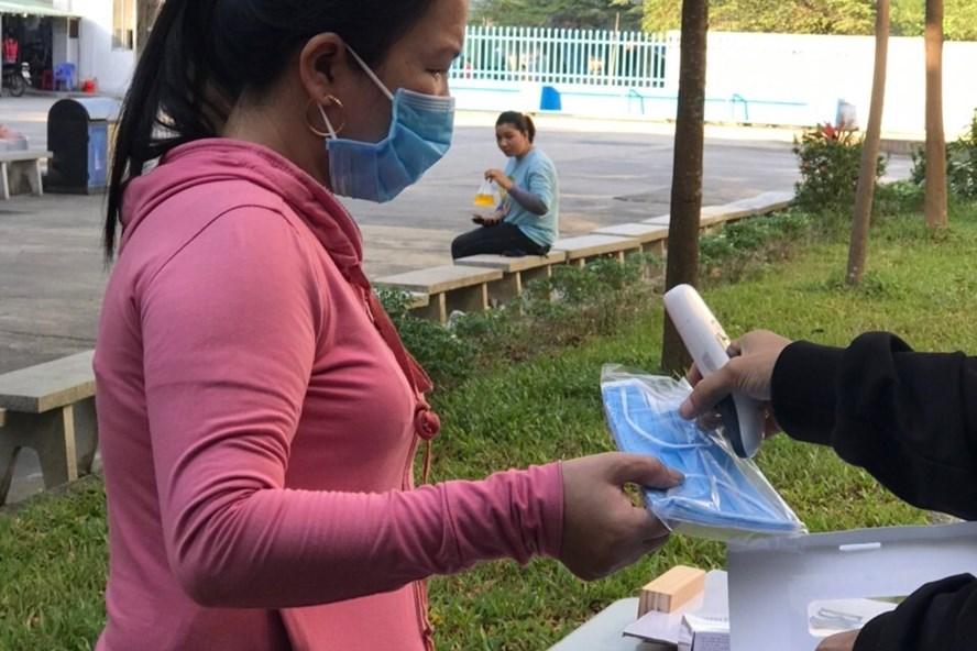 Công ty Vinakad phát khẩu trang và đo thân nhiệt cho công nhân.  Ảnh: Hồ Sỹ Tân