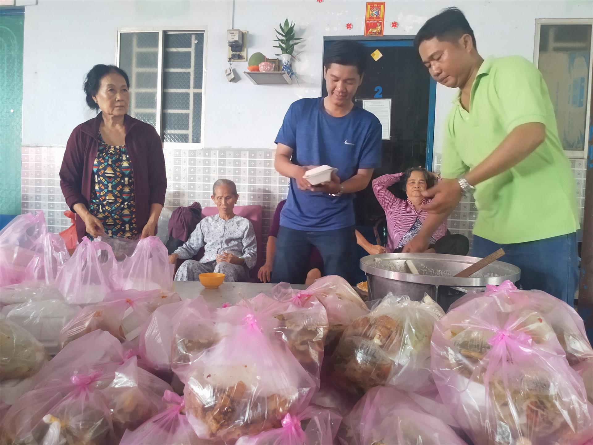 Các tình nguyện viên nam cho cơm vào hộp. Ảnh: K.Q