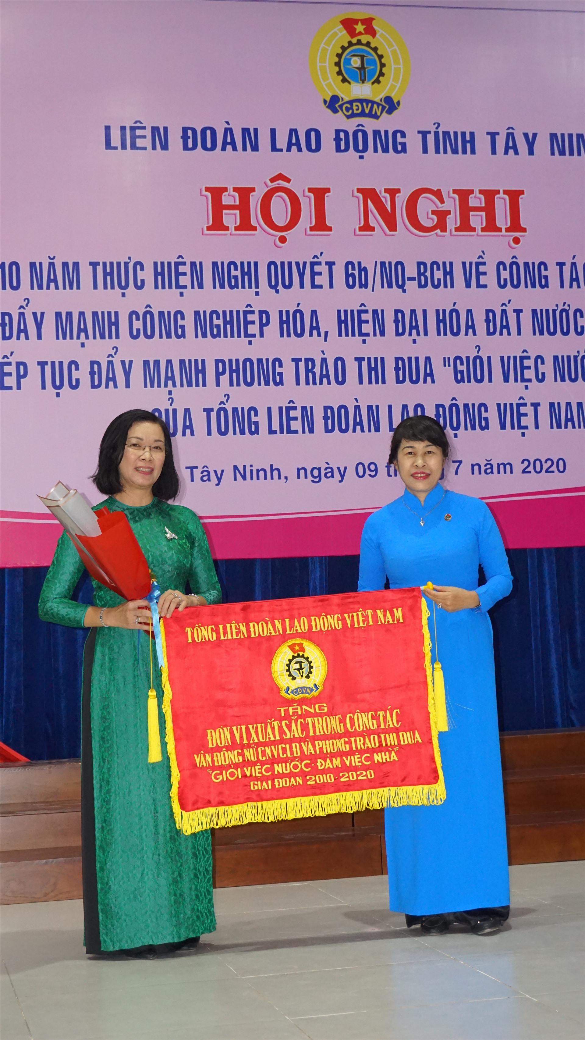 Bà Trịnh Thanh Hằng - Ủy viên Đoàn Chủ tịch, Trưởng Ban Nữ công Tổng LĐLĐ VN trao tặng Cờ thi đua của Tổng Liên đoàn cho tập thể xuất sắc.