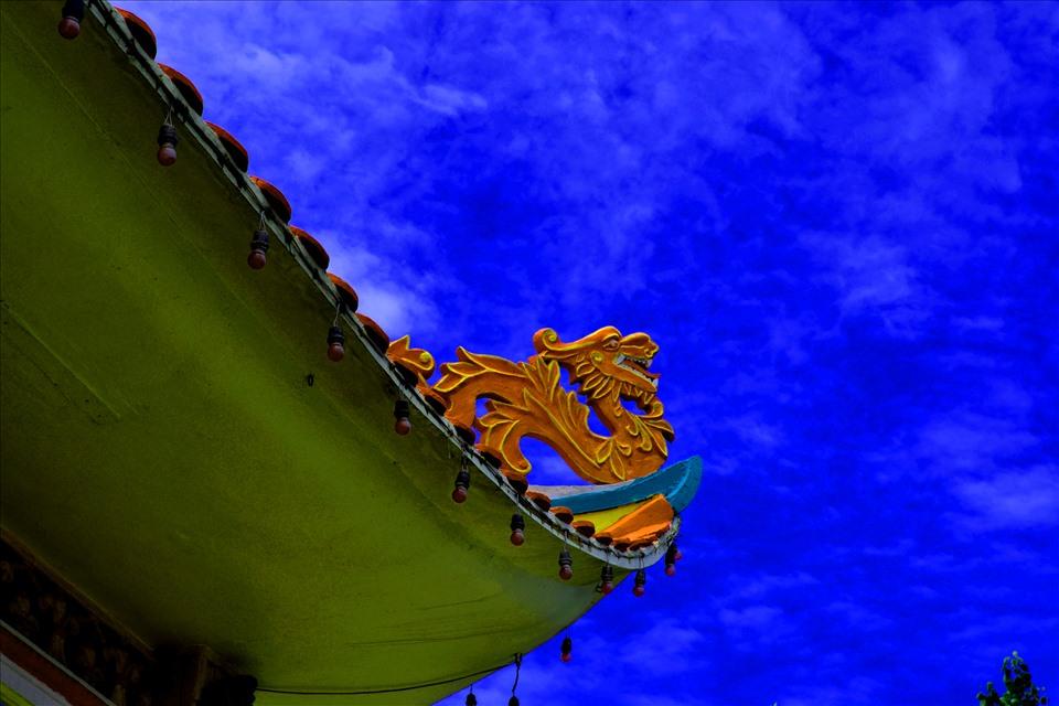 Đặc biệt hơn, các đầu mái đao được thiết kế hình rồng vút lên nền trời xanh như mái của ngôi đình làng. Ảnh: LT