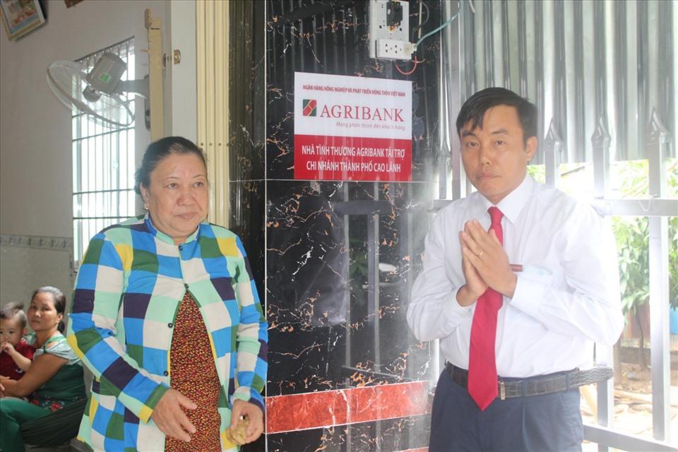 Ông Nguyễn An Bình, Giám đốc Agribank chi nhánh TP Cao Lãnh gắn biển ngôi nhà. Ảnh: Trung Hiếu