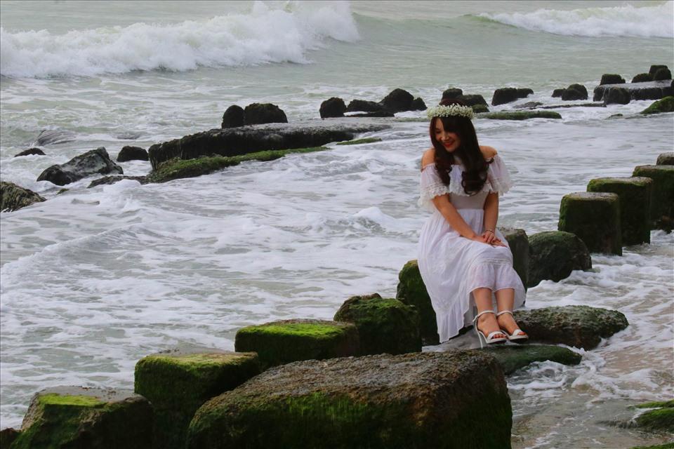 Nhiều chị em tranh thủ lưu lại khoảnh khắc đẹp bên những khung rêu xanh và sóng biển. Ảnh: Phương Linh