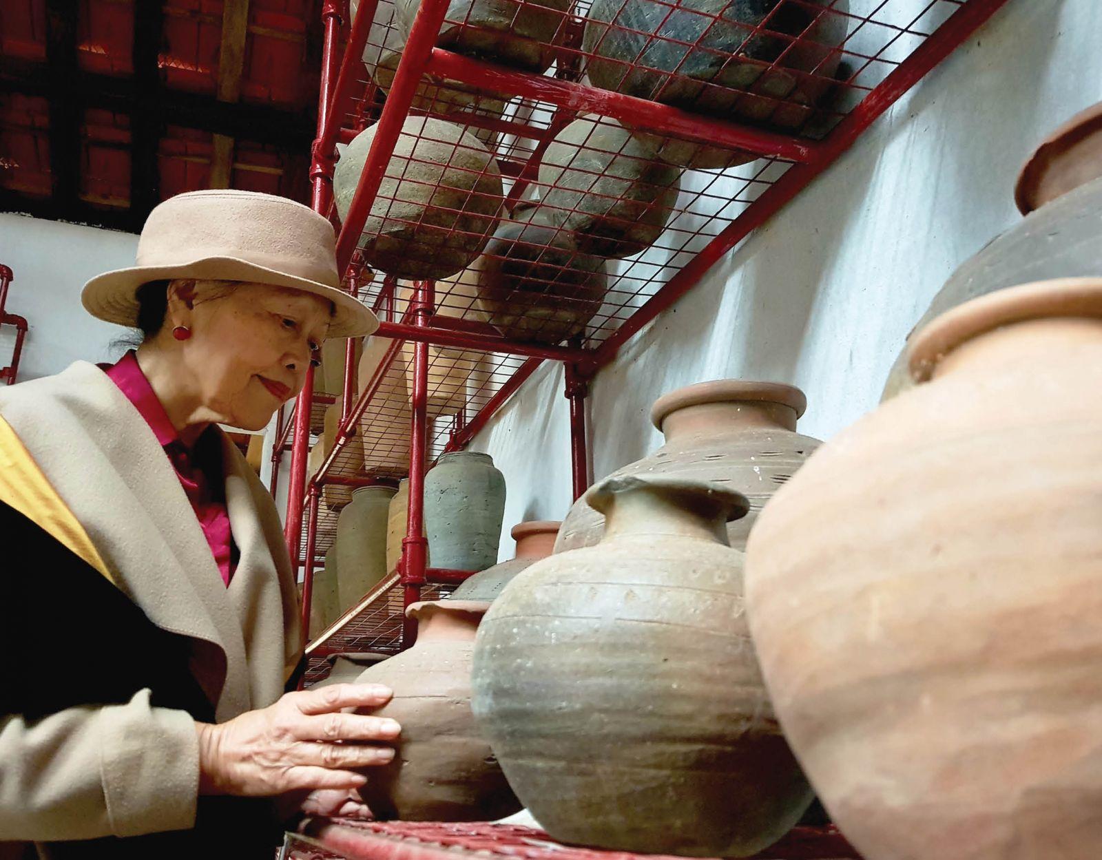Giáo sư Thái Kim Lan và những hiện vật gốm được trục vớt từ sông Hương. Ảnh: Phan Thành