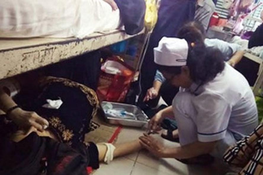 Điều dưỡng cấp cứu cho bệnh nhân ngay trên sàn nhà. Ảnh: VTCnews.
