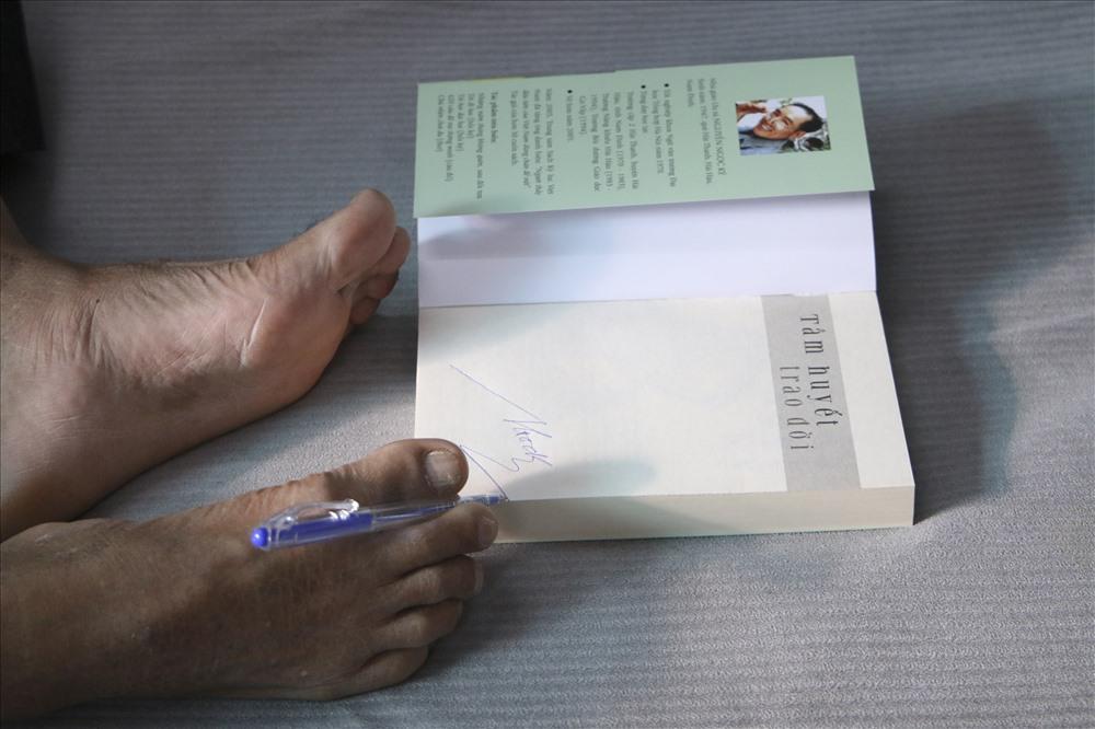 Thầy dùng chân ký tặng sách.