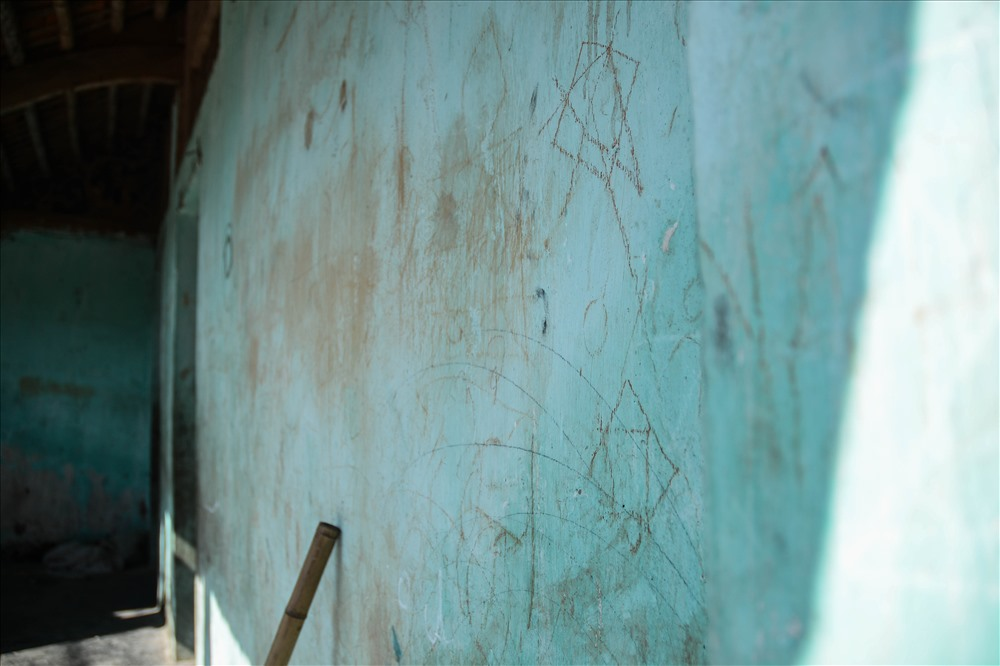 Tường nhà cũ nát chi chít những hình thù loằng ngoằng từ các thế hệ già trẻ trong nhà.