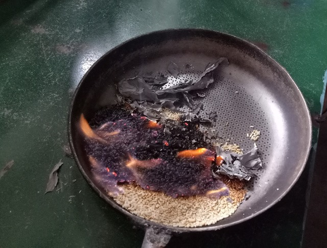 Sau khi rang sơ qua và mang đốt, số gạo hỗ trợ bắt lửa bốc cháy rất nhanh. Ảnh: Dân trí