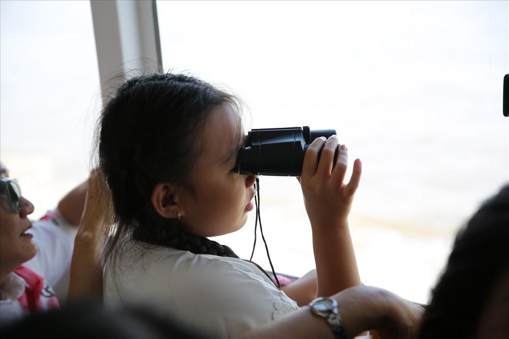 Một em bé trải nghiệm buýt sông và mang theo ống nhòm ngắm cảnh hai bên bờ sông Sài Gòn.  Ảnh: Minh Quân