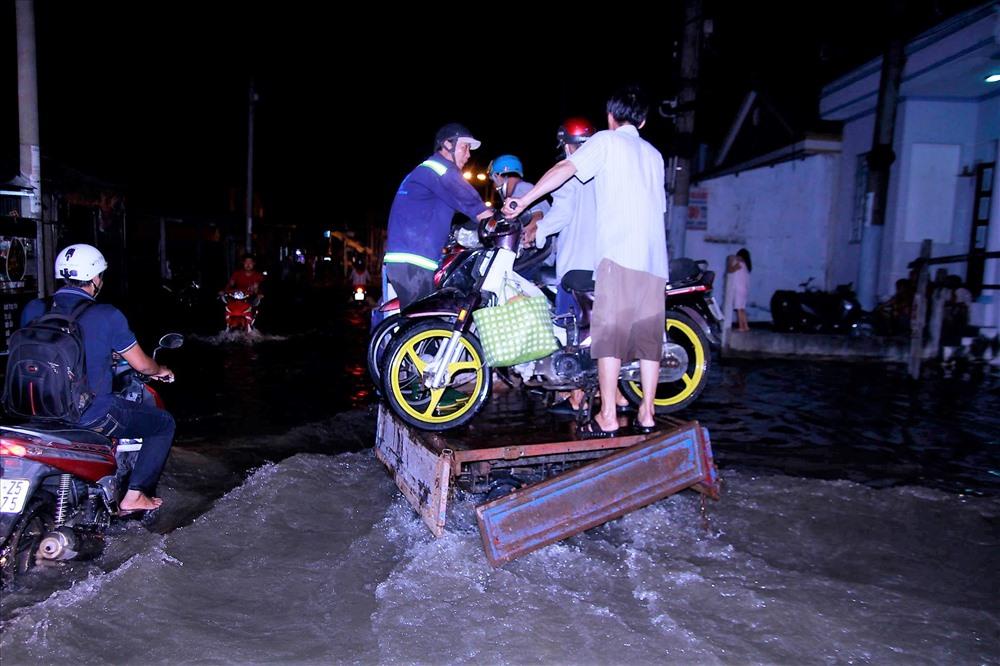 Trong khi chờ giải pháp chống ngập thì người dân Nhà Bè nói chung, dọc đường Lê Văn Lương nói riêng vẫn phải thuê xe chở qua điểm ngập mỗi khi mưa lớn hay triều cường dâng cao. Ảnh: M.Q