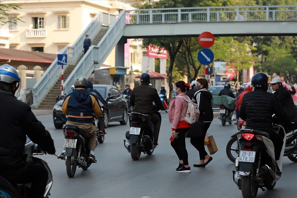 Người đi bộ băng qua đường tại cổng Học viện Ngân hàng, phố Chùa Bộc (Hà Nội). Ảnh: HẢI NGUYỄN